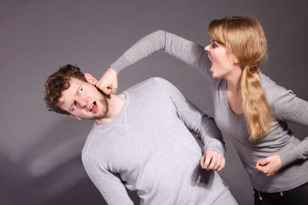 beating: Violence against man. Aggressive woman yelling shouting on scared afraid man. Negative relations in partnership. Expressive young lady beating her partner.