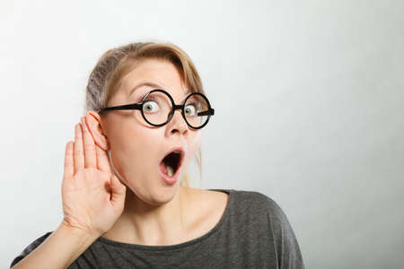 Chatter: Rumors and gossips concept. Newsmonger girl making listening gesture. Shocked surprised gossiping woman. Gossip and chatter. Stock Photo