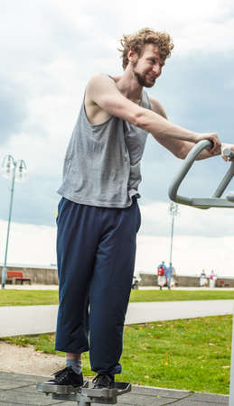 twister: Active young man exercising on twister machine. Muscular sporty guy in training suit working out at outdoor gym. Sport fitness and healthy lifestyle concept.