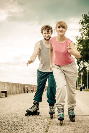 Exercising and competition in sport. Healthy lifestyle and wellbeing. Summertime hobby. Young people race together on rollerblades having fun.