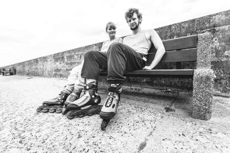 blackwhite: Young people friends in training suit with roller skates. Woman and man relaxing on bench outdoor. Stock Photo