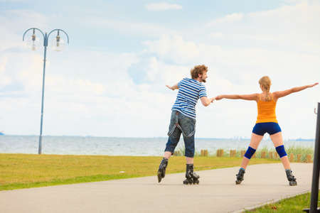 Holidays, active people and friendship concept. Young fit couple on roller skates riding outdoors on sea shore, woman and man rollerblading together on the promenade Stock Photo