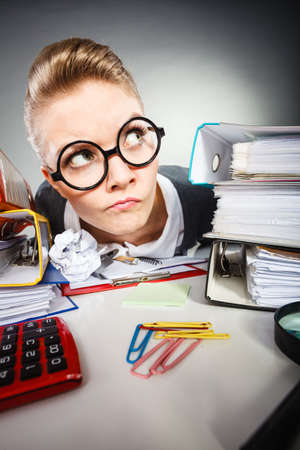 craze: Facial expressions during work. Crazy thoughtful accountant businesswoman surrounded by documents and binders in office. Stock Photo