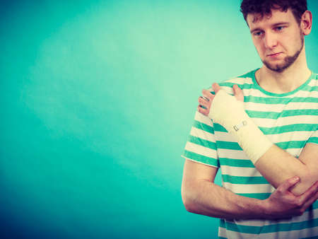 bandaged: Pain and injury concept. Young man holds bandaged hand. Injured part of body. Medicine and healthcare.