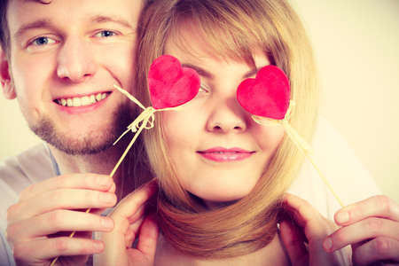 blinded: Love and happiness concept. Cheerful enjoyable young couple with little small hearts on sticks covering woman man eyes. Lovers blinded by their big love. Stock Photo