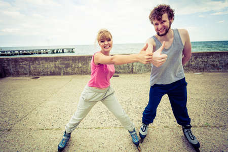 rollerblades: Outdoors activities sport and hobby. Exercises for healthy and strong body.. Friends stretch together have fun riding rollerblades showing thumbs up. Stock Photo