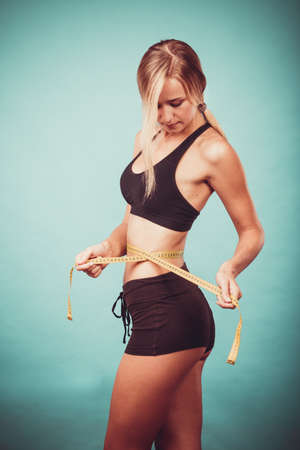 losing control: Weight loss, slim body, healthy lifestyle concept. Fit fitness girl measuring her waistline with measure tape on blue