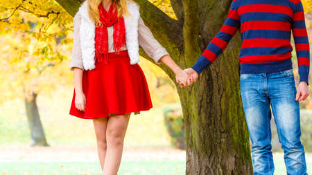 Affection and feelings. Expressing positive emotions. Friendship and love. Young couple meet at park having fun on a romantic date holding hands and walking. Stock Photo
