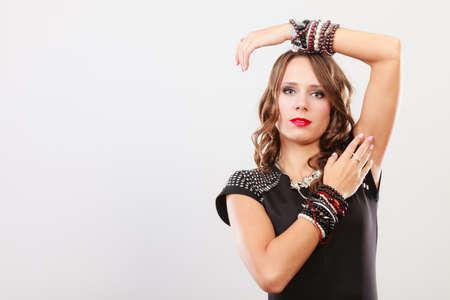 Pretty young woman wearing multiple bracelets jewellery necklace in black elegant evening dress