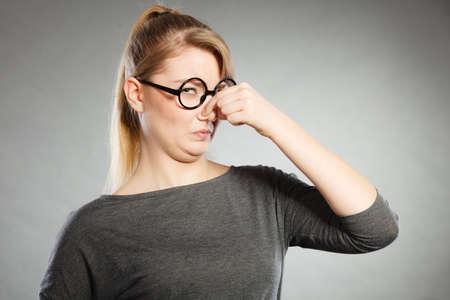 Concepto de mal olor. La mujer joven siente repugnancia pellizca la nariz con los dedos a causa de olor desagradable hedor hedor. reacción facial. Foto de archivo