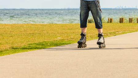 Días de fiesta, el concepto de estilo de vida activo libertad. hombre destinado para jóvenes en patines que montan al aire libre en la costa del mar, chico patinar en un día soleado Foto de archivo