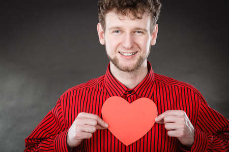 persuade: Love and help from people. Charming lovely man with red paper heart persuade to be good helpful hopeful. Valentines Day or charity concept.