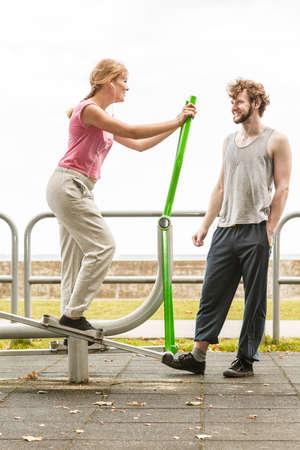 escucha activa: Mujer activa feliz que ejercita en la m�quina el�ptica y el hombre escucha la m�sica en el gimnasio al aire libre. aptitud deporte. Foto de archivo
