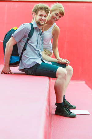 male bonding: Tourism love relationship and dating concept. Young tourist couple with backpack traveling together having fun in city on red stairs