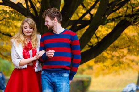 Season, happiness and people concept. Relationships and feelings. Young Couple relaxing in autumnal park enjoy romantic date on sunny day.