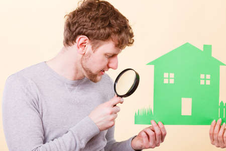 magnifying glass man: Home real estate credit mortgage concept. People with house and magnifying glass. Man and person holding building cutout.