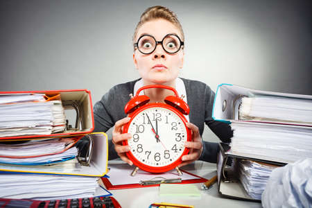 quitting: Corporate job workaholism time concept. Emotional secretary with clock. Nervous female office worker at desk with alarm ringer. Stock Photo