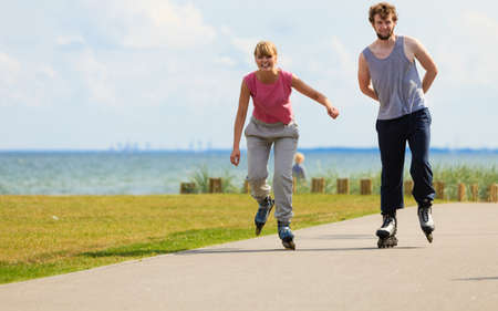 Love romance leisure outdoor fitness sport concept. Teenagers together on skates. Young girl and boy spend time riding rollerskates in park. Stock Photo