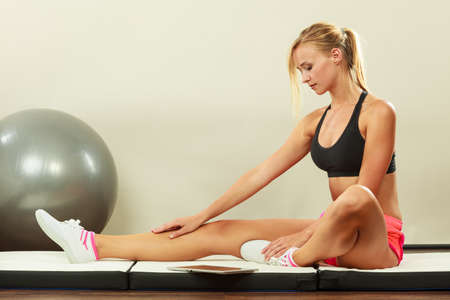 fitball: Fitness woman blonde fit girl sitting on floor and looking into tablet pc
