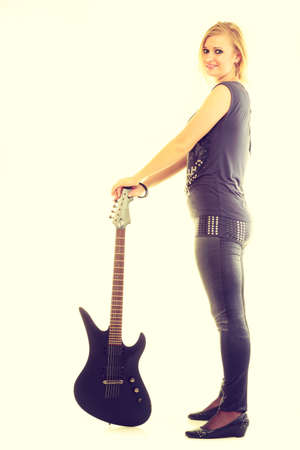 acoustical: Love to music. Young pretty girl with black electric guitar. Blonde woman with passion to playing. Female musician holds instrument. Stock Photo