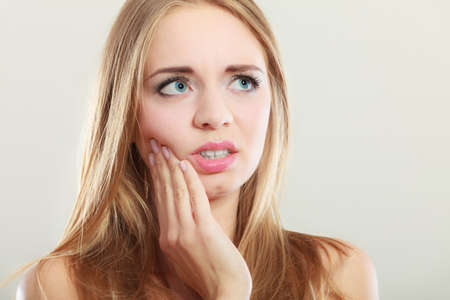 Dental care and toothache. Closeup young woman face worried girl suffering from tooth pain