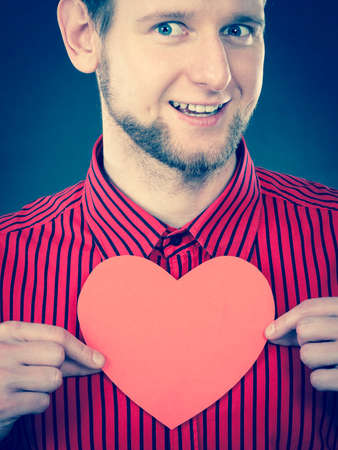 youthful: Feelings affection happiness concept. Cheerful man holding heart. Youthful energetic smiling male holding love symbol cutout.
