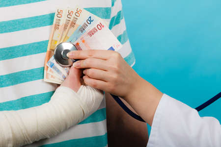 bandaged: Corruption in medicine. Female doctor with stethoscope checking heart beating. Male bandaged hand with banknotes euro money.