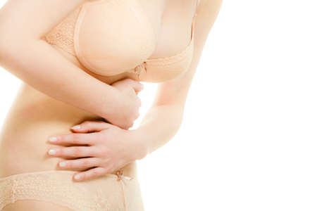 constipation symptom: Bellyache or menstruation. Syndroms of indigestion pregnancy. Closeup woman wearing lingerie suffering from stomach pain isolated on white