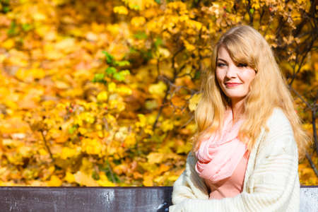 Season, happiness and people concept. Young fashionable blonde woman sitting on bench in autumnal park on sunny day