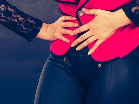 premenstrual: Sickness and diseases. Health problem concept. Young woman in red holding her hands on stomach belly because of strong terrible bad pain ache.