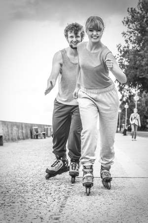 blackwhite: Exercising and competition in sport. Healthy lifestyle and wellbeing. Summertime hobby. Young people race together on rollerblades having fun black and white.
