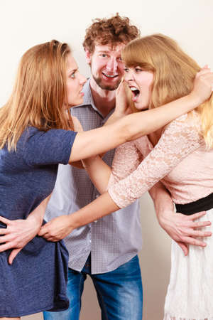 catfight: Aggressive mad women fighting over man. Jealous girls wooing guy. Violence.