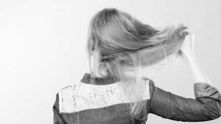 coiffure: Hairstyle and hairdo. Haircare concept. Back view of blonde woman playing with straight long hair. Hairstylist barber making coiffure.