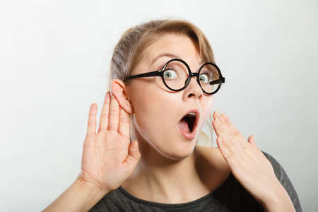 gasping: Hearing gesture shock emotion concept. Shocked girl eavesdropping. Young nerdy stunned lady in glasses listening expressing disbelief gasping. Stock Photo