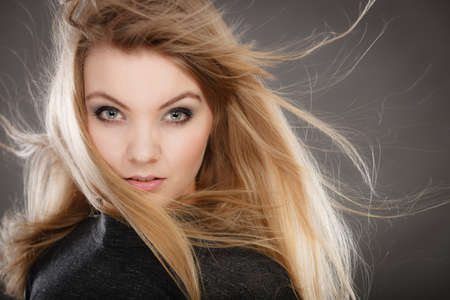 Hairstyle and haircare concept. Portrait of blonde charming attractive young lady with open waving hair. Woman with healthy and beauty hairdo coiffure. Stock Photo