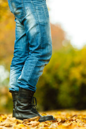 Nature outdoor foliage relax concept. Man in black boots.  Male in leather footwear jeans trousers standing outside. Stock Photo