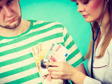 beating: Corruption in medicine. Female doctor with stethoscope checking heart beating. Male bandaged hand with banknotes euro money.