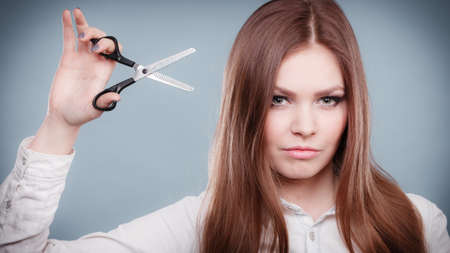 hairstylist: Haircare concept. Cutting and trimming. Young prefessional female barber hairstylist with scissors. Portrait of long haired girl prepared to styling hair.
