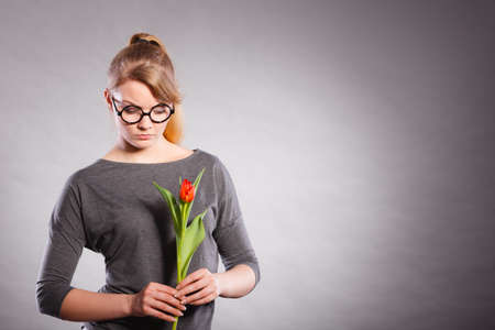 decepción: Disappointment and stress. Young upset student girl with one single red tulip flower on gray grey background. Foto de archivo