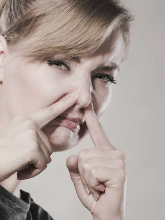 unpleasant: Bad smell concept. Young woman feels disgust pinches her nose with fingers because of odor stench unpleasant stink. Facial reaction.