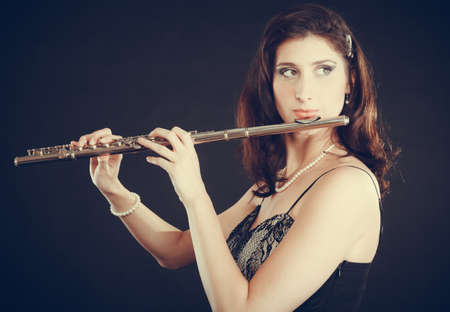 transverse: Music and elegance. Alluring elegant woman playing on transverse flute. Female musician with her instrument performing.
