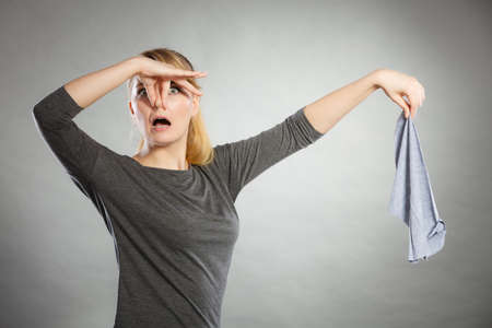 domestic chores: Household duties concept. Young disgust girl holding cleaning cloth rag doing domestic chores. Unhappy housewife.