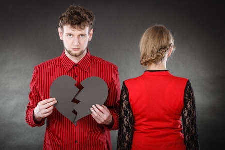 unhappiness: Romance relationship sadness unhappiness misfortune concept. Sad couple with broken heart. Girl with boy together holding black symbol of unhappy love.
