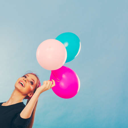 craze: Craziness and lots of fun. Cute crazy joyful girl playing with colored balloons. Blonde playful retro style woman feel craze.