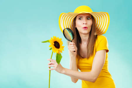 botanist: Botanist woman surprised face expression in yellow hat examining flower looking through magnifying glass on blue background Stock Photo