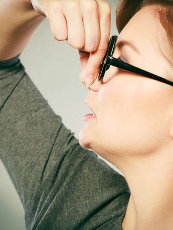 pinches: Bad smell concept. Young woman feels disgust pinches her nose with fingers because of odor stench unpleasant stink. Facial reaction.