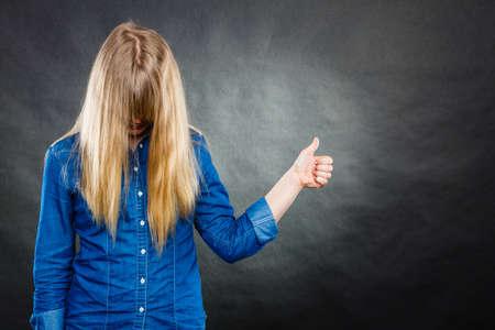 expresion corporal: Positividad y el concepto de éxito. Mujer rubia con la cara cubierta por pelo largo y recto. Muchacha que muestra el pulgar hacia arriba gesto. La expresión corporal. Foto de archivo