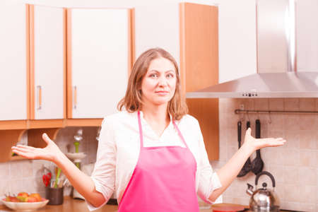 Vision and idea concept. Thinking wondering woman in kitchen. Contemplating housewife wearing pink apron at home.