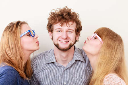 Two pretty women kissing handsome man. Love triangle. Stock Photo