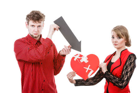 heartbreak: Feelings romance heartbreak making up reconcillation concept. Couple holding love symbols. Young man with woman showing pointer directed at broken fixed heart. Stock Photo